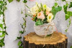Vase de fleurs sur un tronçon en bois Décoration pour la table Image stock