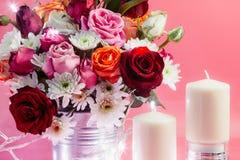 Vase de roses de bouquet au seau en aluminium et au coeur éclatant rouge avec le chandelier blanc sur le fond rose Photographie stock