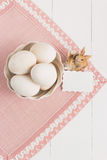 Vase with eggs and napkin on a white background. Selective focus, toned image, film effect, top view. Vase with eggs, napkin and small rabbits on a white Royalty Free Stock Images