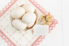 Vase with eggs and napkin on a white background. Selective focus, toned image, film effect, top view. Vase with eggs, napkin and small rabbits on a white Stock Photo