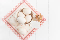 Vase with eggs and napkin on a white background. Selective focus, toned image, film effect, top view. Vase with eggs, napkin and small rabbits on a white Stock Photography
