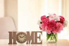 Vase en verre avec de belles pivoines et horloge décorative Photo libre de droits