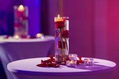 Vase en verre avec des bougies de l'eau et de lumière de roses rouges Image libre de droits