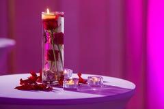 Vase en verre avec des bougies de l'eau et de lumière de roses rouges Images stock