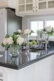 Vase en verre de fleur sur le compteur noir de granit Images stock