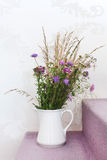 Vase with field flowers against wallpaper wall Royalty Free Stock Image