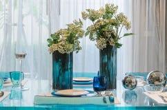 Vase of flower on glass dinning table Stock Photo