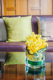 Vase flower on table with pillow on sofa Stock Photos