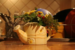 Vase with flowers. Small elephant vase with flowers staying on the table top in the kitchen Stock Image