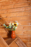 Vase with flowers bouquet on the stairs with wooden background. Vase with different flowers bouquet on the stairs with wooden background stock images