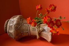Vase with flowers. Clay vase with a pattern and red flowers on a red background stock photo