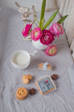 A vase of flowers and a cup with milk and cookies Stock Images