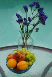 Vase with flowers and fruit by the pool Stock Images