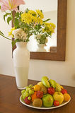 Vase of flowers and fruit on a table. Bowl of fruit and vase of flowers with reflection in mirror on a table Royalty Free Stock Photography
