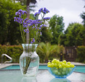 Vase with flowers and grapes by the pool. Vase with blue flowers and grapes stay on glass table by the pool Royalty Free Stock Photography