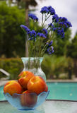 Vase with flowers and peaches by the pool. Vase with blue flowers and peaches stay on glass table by the pool Stock Photos