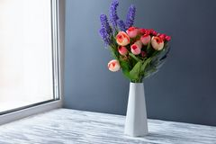 Vase with flowers purple lilac lavender on the window. Vase with flowers purple lilac lavender in a beautiful white vase on the wooden background of the news and stock photo