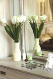 A vase of flowers on the table with a mirror Stock Photography
