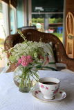 Vase of flowers and tea cup on sunroom tale. Peaceful morning with first cup of coffee in floral china cup on table in sunroom, with pretty floral arrangement as royalty free stock photos