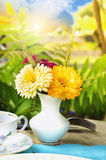 Vase with flowers on tea table in sunny garden . Royalty Free Stock Images