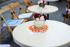 Vase with flowers white table in cafe outdoors street. royalty free stock images