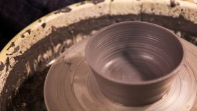 Vase from fresh clay turn twirl potters wheel. Sculptor in workshop makes jug out of clay closeup royalty free stock photo
