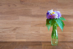 Vase with hand picked flowers on wood Royalty Free Stock Photo
