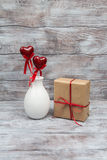 Vase with hearts on stick and gift for Valentines Day Stock Photography