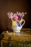 Vase with hyacinths. White vase with hyacinths placed on wooden old box stock photography
