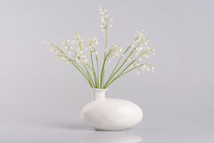 Vase with lilies of the valley  on white Stock Image
