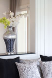 Vase med konstgjorda blommor i vardagsrum Arkivbild