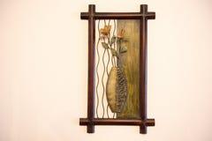 Vase mit Blumen Kunstschaffung vom Metall und vom Holz auf der Wand stockbild