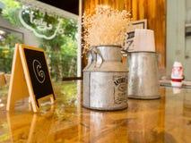 Vase mit Eisen und sechs Zahl auf dem Tisch gemacht von hölzernem, Weinleseart in den Kaffeestuben Lizenzfreie Stockbilder