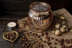 Vase mit gepresster Blume, Kaffee und zerstreuten Röstkaffeebohnen Stockbild