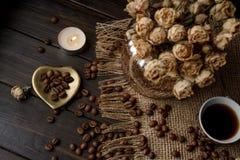 Vase mit gepresster Blume, Kaffee und zerstreuten Röstkaffeebohnen Stockbilder