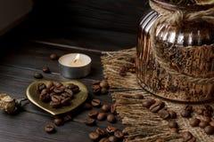 Vase mit gepresster Blume, Kaffee und zerstreuten Röstkaffeebohnen Lizenzfreies Stockfoto