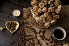 Vase mit gepresster Blume, Kaffee und zerstreuten Röstkaffeebohnen Stockfoto