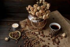Vase mit gepresster Blume, Kaffee und zerstreuten Röstkaffeebohnen Lizenzfreies Stockbild
