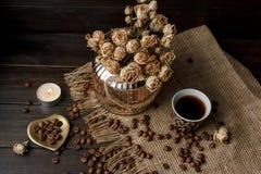 Vase mit gepresster Blume, Kaffee und zerstreuten Röstkaffeebohnen Lizenzfreie Stockfotos
