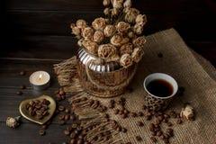 Vase mit gepresster Blume, Kaffee und zerstreuten Röstkaffeebohnen Lizenzfreie Stockfotografie