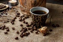 Vase mit gepresster Blume, Kaffee und zerstreuten Röstkaffeebohnen Stockfotografie