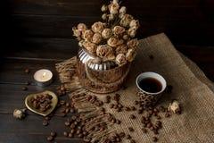 Vase mit gepresster Blume, Kaffee und zerstreuten Röstkaffeebohnen Lizenzfreie Stockbilder