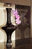 Vase mit Orchideeblume in der braunen Nische Lizenzfreie Stockfotos