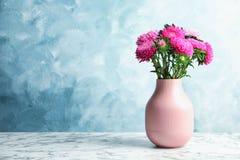 Vase mit schönem Asterblumenblumenstrauß auf Tabelle gegen Farbhintergrund stockfotos