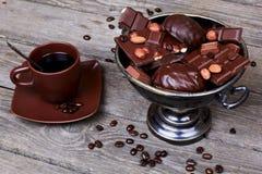 Vase mit Schokolade, Nüssen und Kaffee auf einem grauen hölzernen Hintergrund Stockfotografie