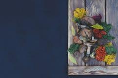 Vase mit trockenen Blättern, Apfel und Kerzen auf dem Rausschmiß stockfoto