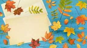 Vase mit trockenen Blättern, Apfel und Kerzen auf dem Rausschmiß Bunte Blätter des Falles gestalteten Papier auf hölzernem Hinter Lizenzfreie Stockfotos