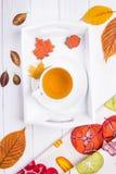 Vase mit trockenen Blättern, Apfel und Kerzen auf dem Rausschmiß Kräutertee, Herbstlaub und Lebkuchen in Form von Ahornblatt und  Stockfotografie