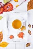 Vase mit trockenen Blättern, Apfel und Kerzen auf dem Rausschmiß Kräutertee und Herbstlebkuchen in Form von Ahornblatt und Eichel Lizenzfreie Stockfotos