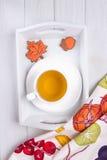 Vase mit trockenen Blättern, Apfel und Kerzen auf dem Rausschmiß Kräutertee und Herbstlebkuchen in Form von Ahornblatt und Eichel Stockfotografie